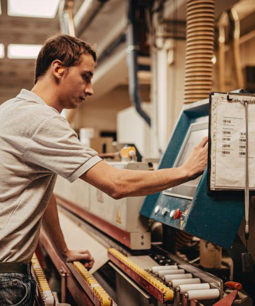 Mitarbeitern beim Arbeiten an einer Maschine in der Tischlerei
